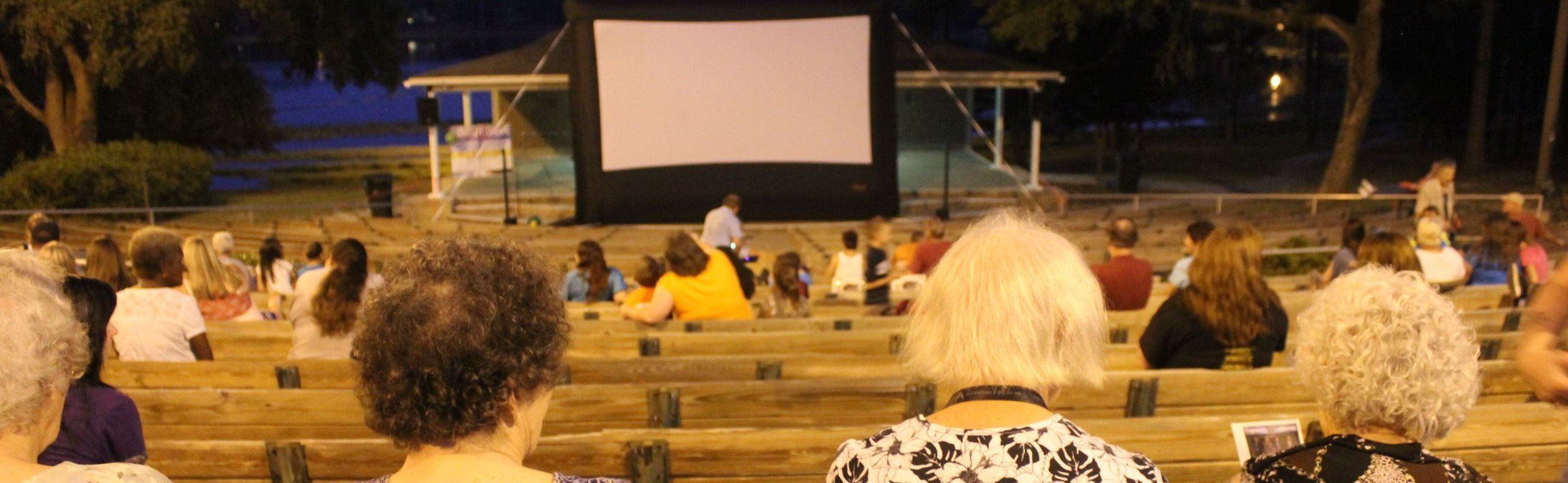 People watching an outdoor movie in an amphitheater