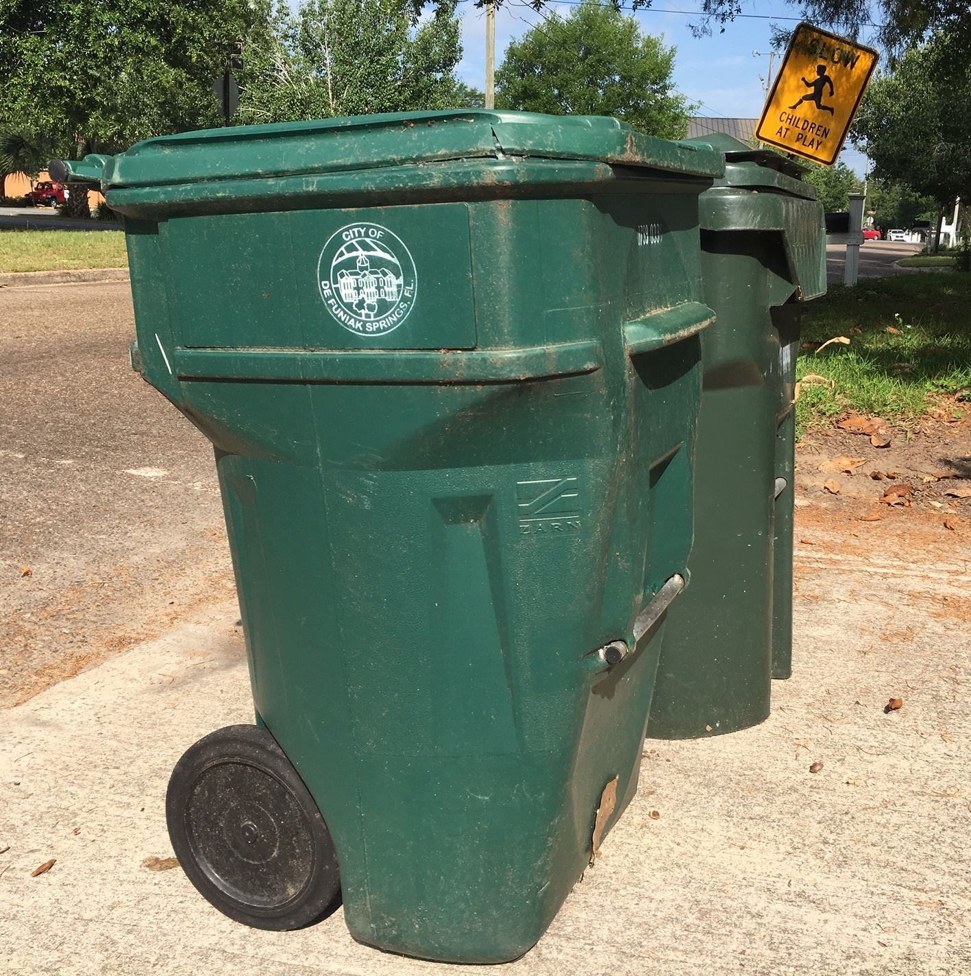 Plastic container four feet tall and two feet wide with a handle and two plastic wheels for garbage