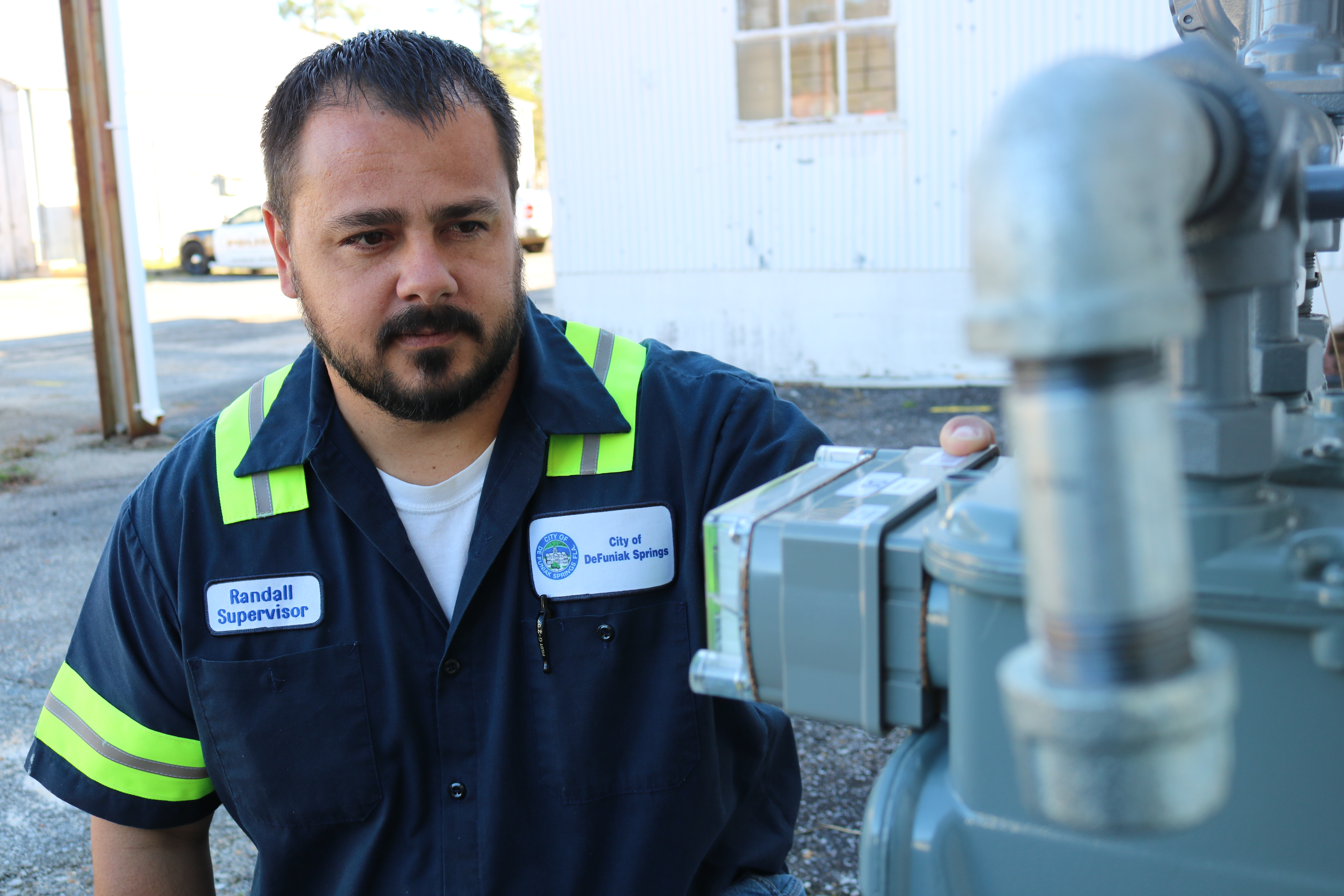 Man in public works uniform looking at a natural gas meter