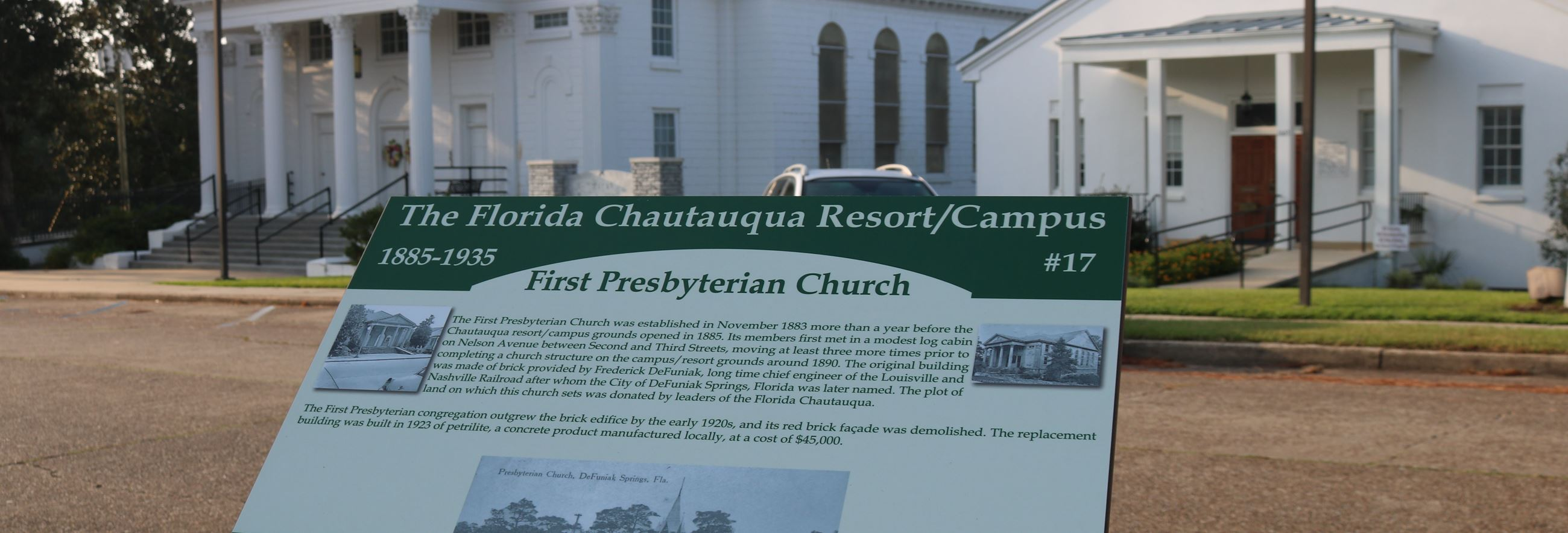 information panel in front of a large white stone church