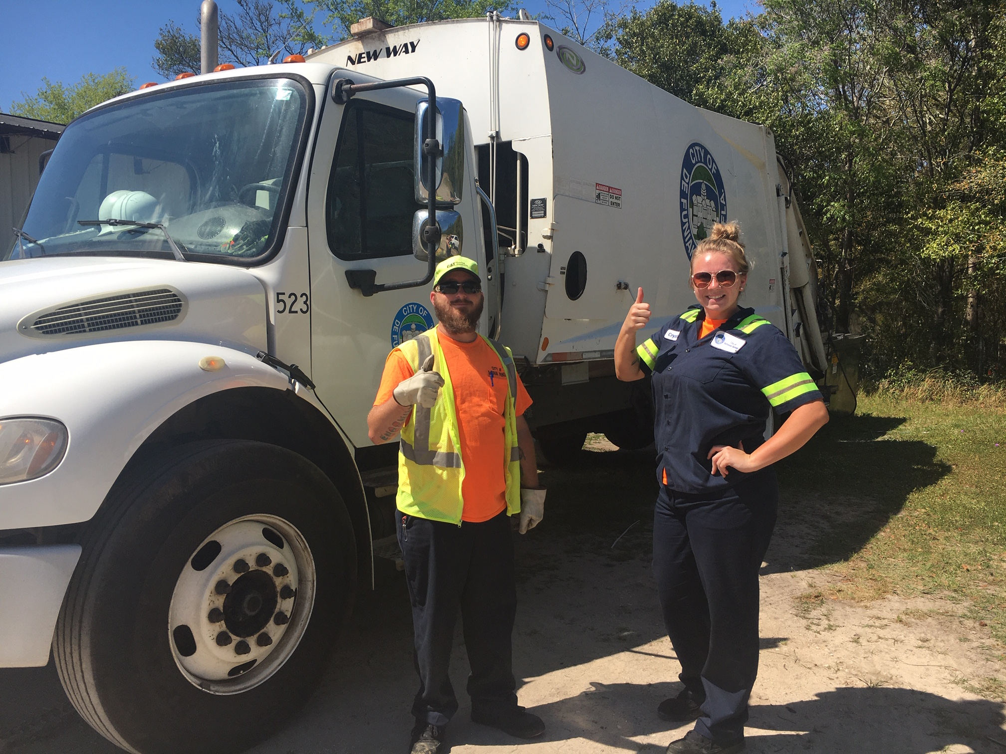 male and female sanitation workers in front of a garbage truck with thumbs up