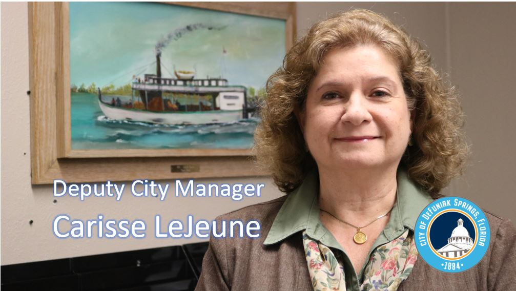 Lady standing in front of a painting of an old steam boat with words Deputy City Manager Carisse LeJ