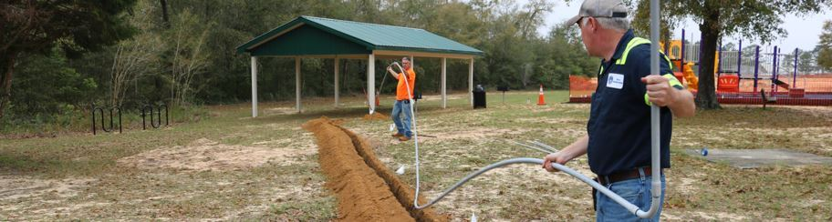 Two men placing flexible conduit into the ground