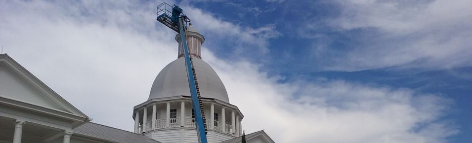 Man in a ginny boon at top of dome of large building which looks like US Capitol
