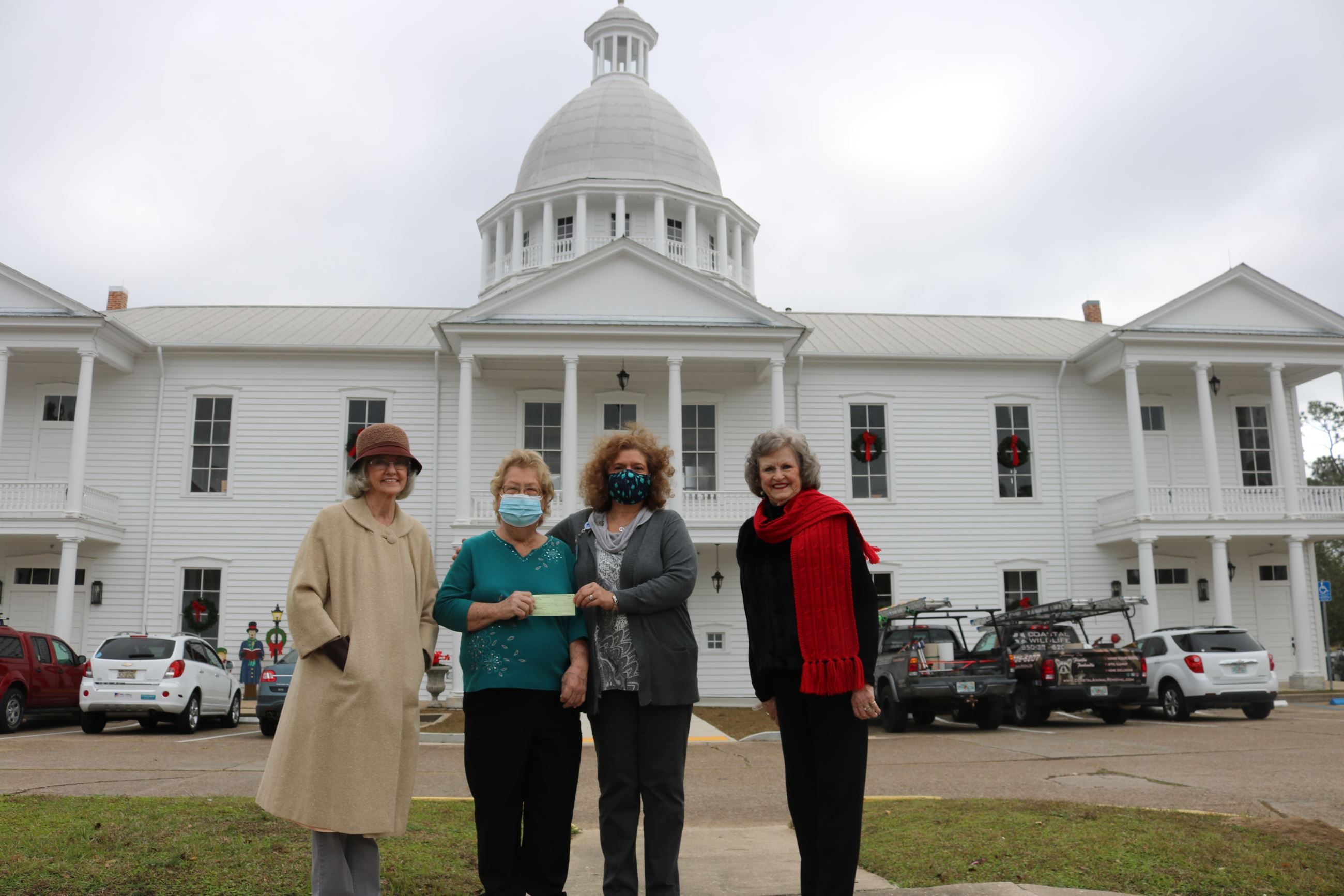 Four ladies in front a large historic building where one is presenting a check to another.